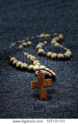 Rosary in a black sand close up photo