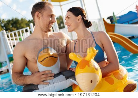 Affectionate looks. Adorable young couple standing in the swimming pool, wearing animal-shaped swim rings and looking at each other with affection