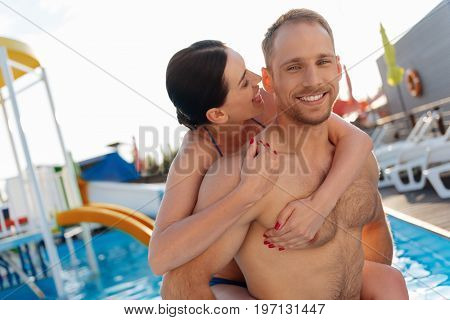 Love games. Pretty young woman standing in the swimming pool and hugging her husband from behind and being about to bite his ear while he smiling at the camera happily
