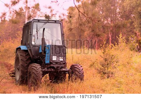 Old tractor in the field. Autumn shot.