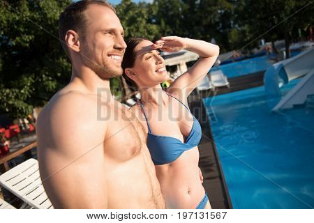 Who is there. Pleasant young couple standing near the swimming pool and looking into the distance as if having seen someone familiar while the woman covering eyes from sun