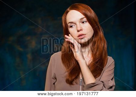 young fashionable attractive redhead girl in brown shirt posing. beauty model woman with luxurious red hair. hairstyle. holiday makeup