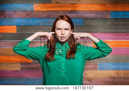 young emotional redhead teen covering with fingers by her ears. she wearing in green blouse over color wooden background