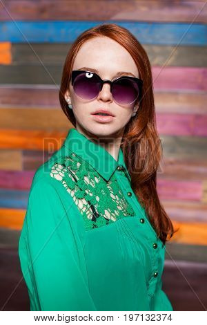 attractive young redhead girl in greem blouse and sunglasses over color wooden background. beauty model woman with luxurious red hair. hairstyle