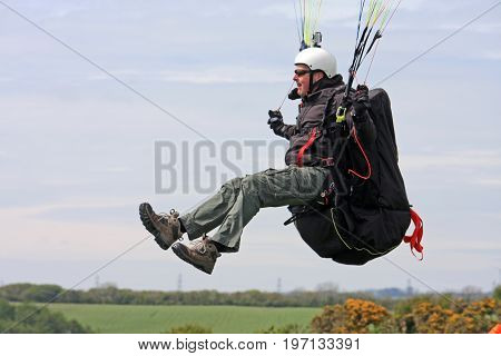 paraglider launching from the top of a hill
