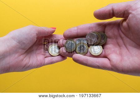 Men's and women's palms with coins. The man passes the coins to the woman. Lack of money. Family budget.