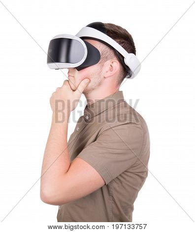 Close-up portrait of a thoughtful man experiencing virtual reality, isolated on a white background. A man with professional virtual reality glasses. New reality video game. A guy in a virtual helmet.