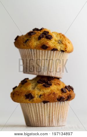Couple of tasty homemade vanilla muffins with chocolate chunks on bright white background. Closeup.