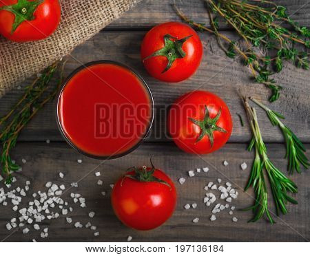 Freshly squeezed Tomato juice in glass. Ingredients for Tomato juice are crystalline salt, cherry tomatoes, rosemary greens and thyme on burlap. Rustic vintage gray wood background. Top view.