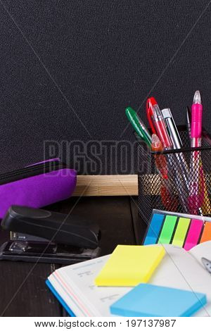 Pencil case with various stationery on old wooden table on blackboard background