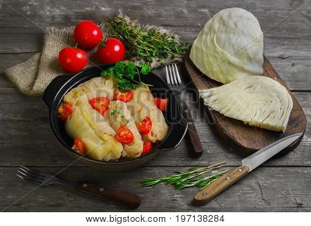 Cabbage rolls with meat and rice in bowl. Fresh cut cabbage and cherry tomatoes, greenery for cooking cabbage rolls with meat. Cabbage rolls on gray wooden rustic background.