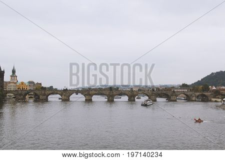 Prague, Czech Republic, October 2016, Historic Charles Bridge and Vltava river at cloudy day, wide angle