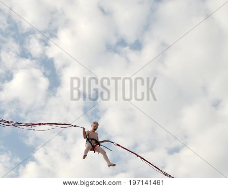 ANAPA, RUSSIA - JUNE 25, 2017: Children's rest. Joyful boy with blond hair opening his mouth wide shouting with happiness, flying up into blue cloudy sky in an air attraction. Vertical frame