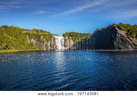 Sunny autumn day. The vast blue lake and powerful waterfall Montmorency in Montmorency Falls Park, in vicinities Quebec. The concept of cultural and active tourism