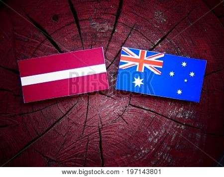 Latvian Flag With Australian Flag On A Tree Stump Isolated