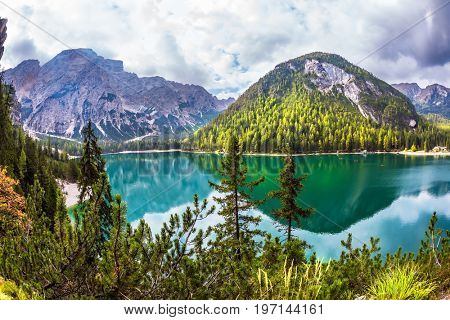South Tyrol. Magnificent lake Lago di Braies. Green water reflects the surrounding mountains and forest. The concept of walking and eco-tourism