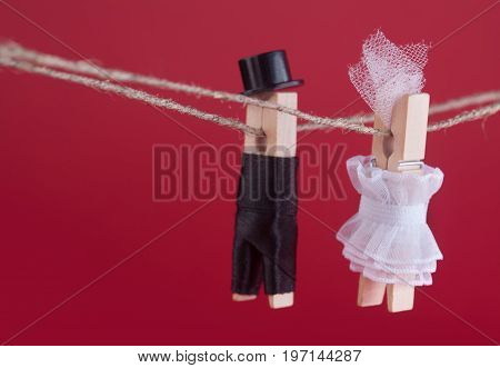 Bride and groom clothespin toys on clothesline. Abstract woman in white wedding dress and man with suit hat. Love concept photo. Macro view, shallow depth of field, red background.