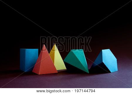 Colorful abstract geometric shape figures still life. Three-dimensional pyramid prism rectangular cube on black blue background. Yellow blue pink malachite colored objects textured paper surface