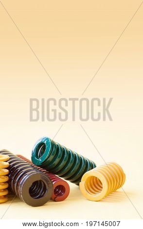 Colorful steel spirals, pressure springs set with different hardness flexibility and size. metallic coil wire objects on gradient background. Macro, shallow depth field. Copy space, vertical photo.