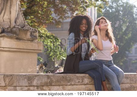Two happy girls sitting near the monument in the downtown and blowing bubbles. One girl is black. Casual lifestyle concept.