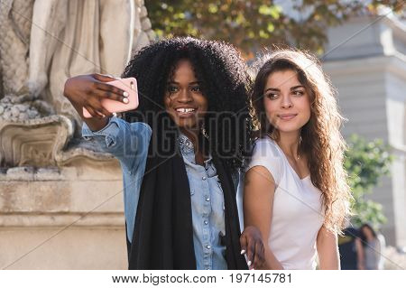 Close up shot of two beautiful girls making selfie near the monument. One girl is black with long black curly hair.