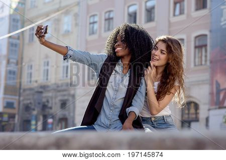 Two sexy and attractive women maling selfie in the beautiful street. One woman is black with long curly hair.