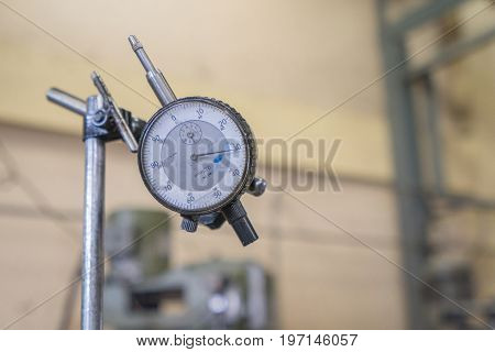 Dial indicator gauge with industrial factory background