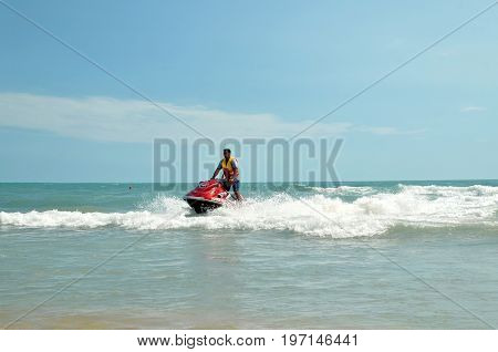 ANAPA, RUSSIA - JUNE 25, 2017: Beach vacation on sea coast. Brutal man in a life jacket, standing on a hydrocycle, skating among sea waves on a summer sunny day