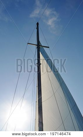 Fragment of mast of sea cruise yacht with raised sail against blue sunny sky, sun and light white clouds. Backlight. Closeup