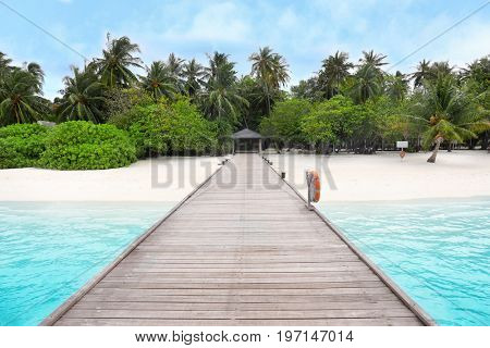 View of wooden pontoon and sea beach at resort on summer day