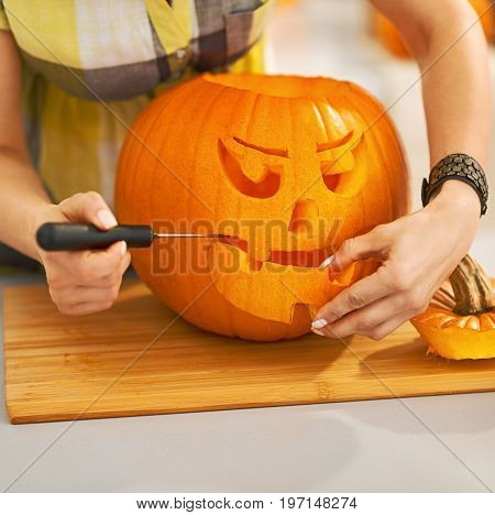 Closeup On Housewife Carving A Big Orange Pumpkin Jack-o-lantern