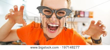 Smiling Young Woman In Halloween Decorated Kitchen Frightening
