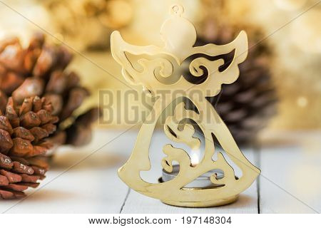 Golden figure of Christmas angel pine cones sparkling luminous background festive greeting card template copy space
