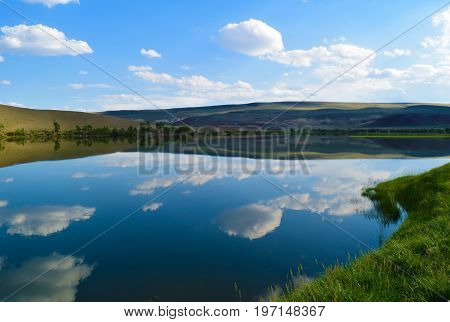 Landscape of calm lake hills green grass and blue sky in Altai mountains. White clouds reflected in water. Chuya prairie Altay Republic Siberia Russia.