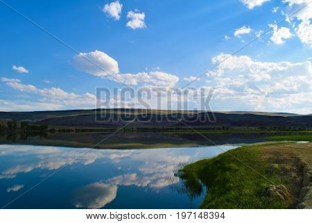 View of calm lake hills green grass and blue sky in Altai mountains. White clouds reflected in water. Chuya steppe Altay Republic Siberia Russia.