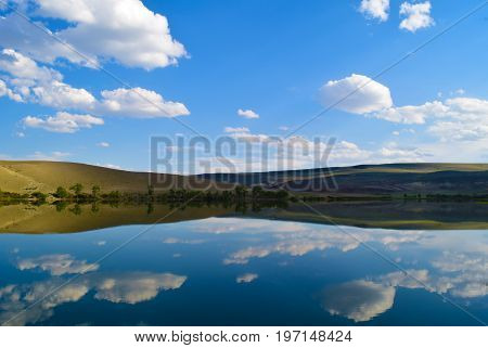 Scene of calm lake yellow hills and blue sky in Altai mountains. White clouds reflected in water. Chuya steppe Altay Republic Siberia Russia.