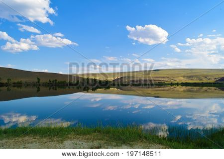 View of quiet lake hills green grass and blue sky in Altai mountains. White clouds reflected in water. Chuya prairie Altay Republic Siberia Russia.