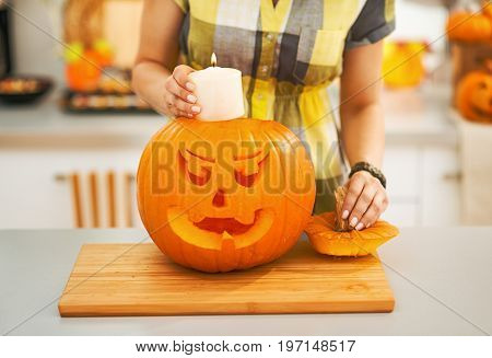 Closeup On Woman Putting Candle Inside Pumpkin Jack-o-lantern