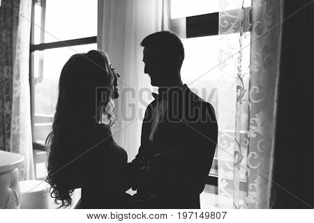 Moment of first meeting of groom and bride on their wedding day. Newlyweds stand near the window in the shade and smile at each other Black and white photo