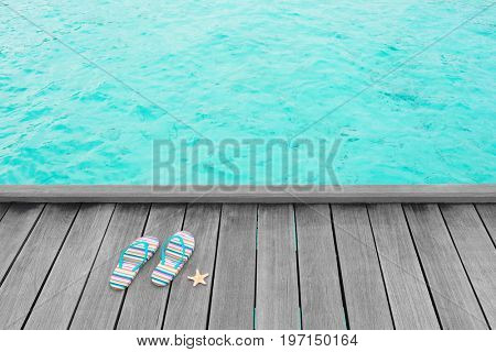 Flip-flops and starfish on wooden pontoon at sea resort. Summer vacation concept