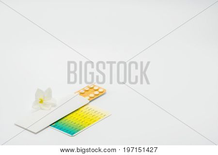 Contraceptive pills with flower on white background
