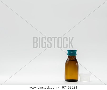 Antipyretic syrup in amber bottle with blank label and a plastic measuring cup on white background