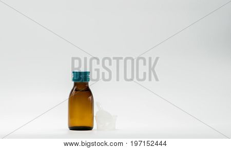 Cough syrup in amber bottle with blank label and a plastic measuring cup teaspoon on white background