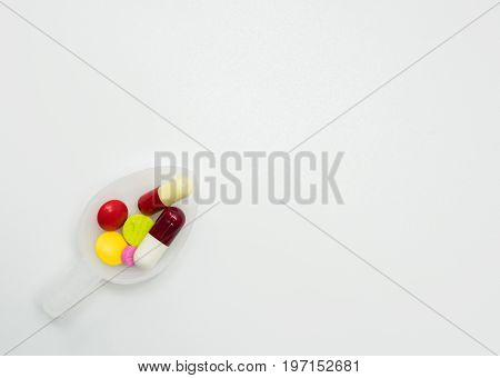 Colorful pills in teaspoon on white background