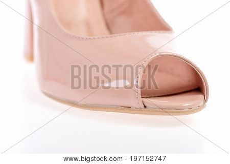Womens patent leather shoe close up. Fashion and beauty concept. One shoe in pink colour. Female sandal isolated on white background. Summer accessories: high heel sandals.