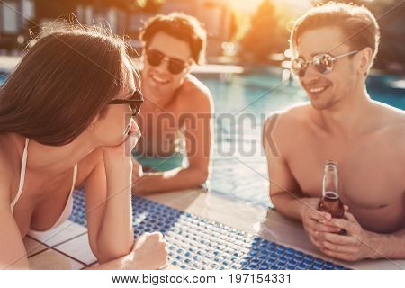 Group of young friends is having fun near swimming pool together drinking beer and smiling.