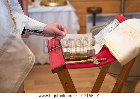 church utensil on an altar glans cross on the church altarthe Bible on the table ceremony of water christening priest holds a bible on a table