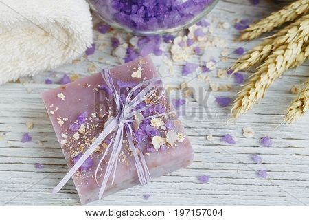 Natural handmade soap sea salt towel oat flakes and wheat ears on a white wooden background.