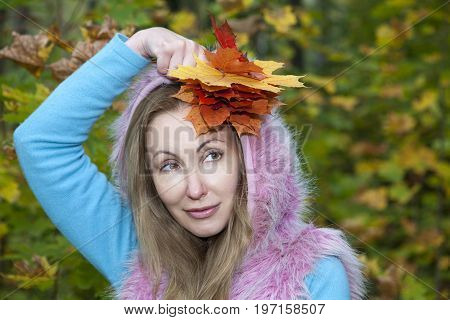 The beautiful woman in autumn park with maple leaves