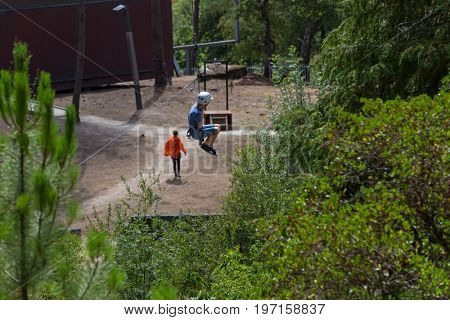 MEZIO, PORTUGAL - JULY 22, 2017: young adventurous kid doing a slide in zip lining thru the forest. July 22, 2017, Mezio, Portugal.